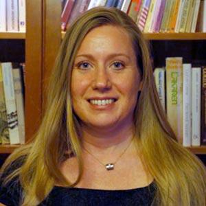 Porträtt på Åsa Colliander-Celik som står framför en bokhylla.